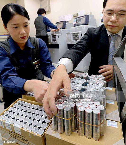 Officials stock up on 1yen coins as the new 8 percent consumption tax launch at the Keihan department store outlet on April 1 2014 in Moriguchi Osaka...