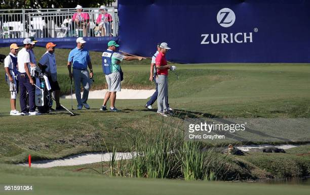 Officials talk with the group of Andrew Landry and Talor Gooch as alligators are seen in the bunker on the 18th hole during the first round of the...