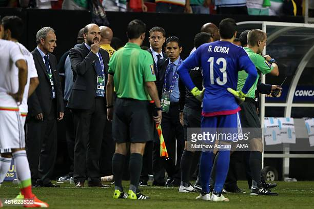 CONCACAF officials talk with the referees as players from Panama walk off the field in protest after a last minute penalty was awarded in the last...