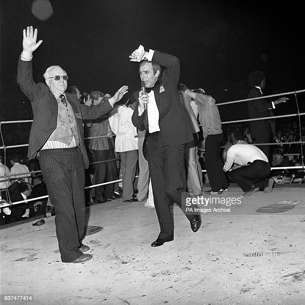 Officials trying to dodge flying objects after the unhappy crowd started to toss empty beer bottles into the ring following an early retirement by...