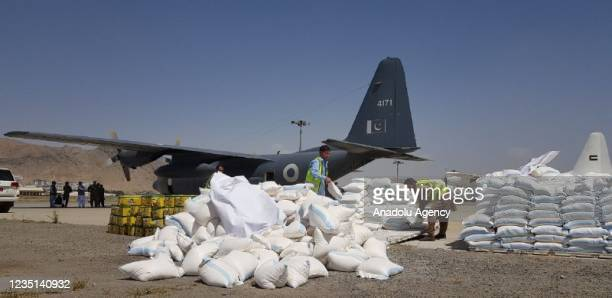 Officials unload packages as Pakistani cargo aircraft carrying humanitarian aid arrives at Hamid Karzai International Airport in Kabul, Afghanistan...