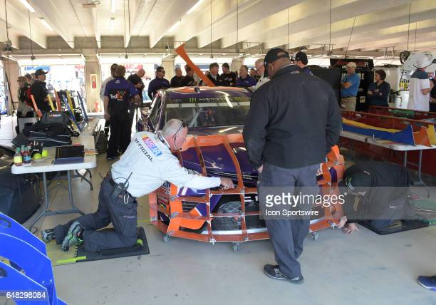 Officials use the Claw to inspect the front end of the car for Denny Hamlin Joe Gibbs Racing FedEx Ground Toyota Camry before the Monster Energy...