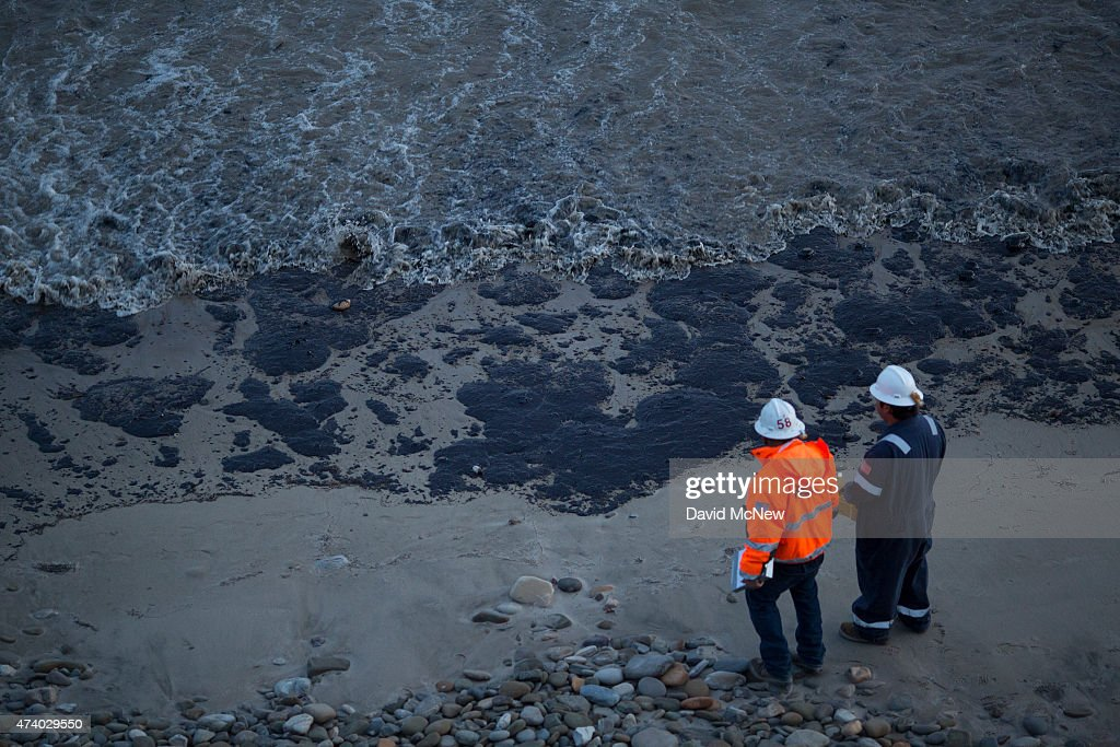 Officials walk along an the oil-covered beach on May 19, 2015 north of Goleta, California. About 21,000 gallons spilled from an abandoned pipeline on the land near Refugio State Beach, spreading over about four miles of beach within hours. The largest oil spill ever in U.S. waters at the time occurred in the same section of the coast in 1969 where numerous offshore oil platforms can be seen, giving birth to the modern American environmental movement.