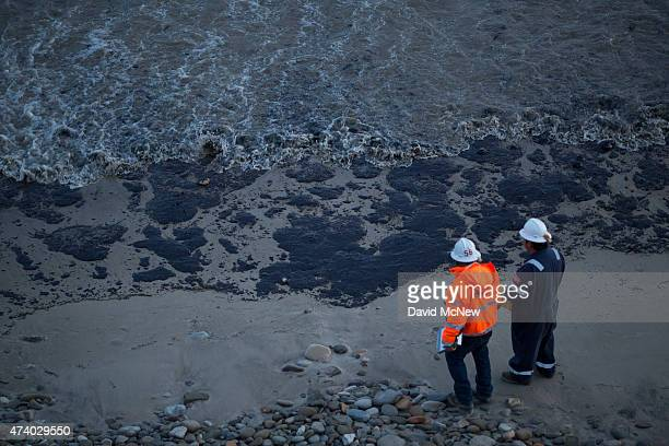 Officials walk along an the oilcovered beach on May 19 2015 north of Goleta California About 21000 gallons spilled from an abandoned pipeline on the...