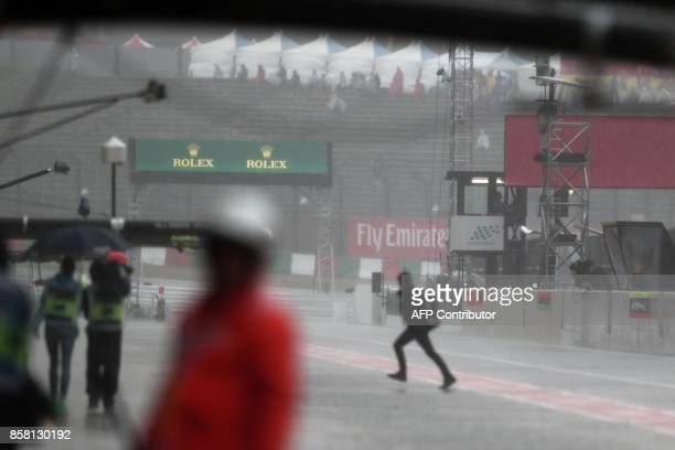 Officials walk in the pit lane as heavy rain delays the second practice round of the Formula One Japanese Grand Prix at Suzuka on October 6, 2017. /...