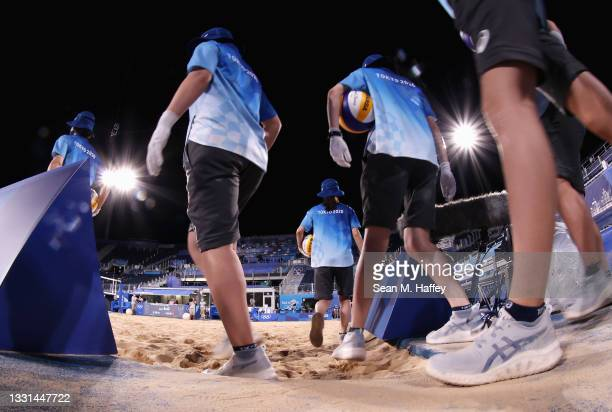 Officials walk onto the court before the game between Team Cuba and Team Italy during the Women's Preliminary - Pool E beach volleyball on day seven...