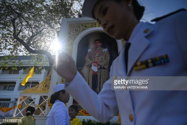 Officials walk past a portrait of Thailand's King Maha Vajiralongkorn in front of the Grand Palace ahead of his coronation in Bangkok on May 4 2019