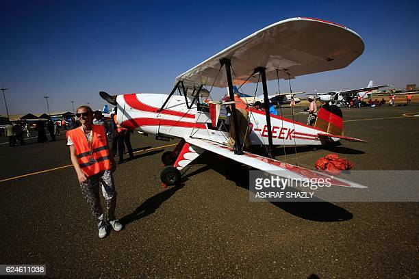 Officials walk past the vintage Bucker Bu 131 biplane as it sits on the runway on November 20 2016 in Khartoum airport during the Vintage Air Rally A...