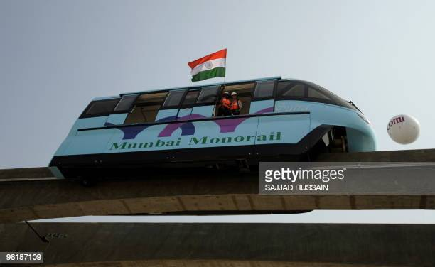Officials wave the Indian national flag during the trial run of the first Monorail in Mumbai on January 26 2010 The Malaysiabased Scomi Group in...