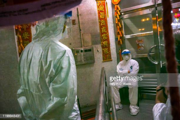 Officials wearing protective gear sit guard outside an entrance to the Hong Mei House residential building at Cheung Hong Estate in the Tsing Yi...
