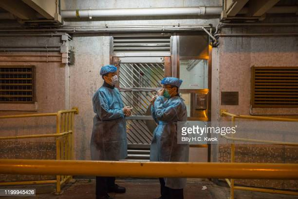 Officials wearing protective gear stand guard outside an entrance to the Hong Mei House residential building at Cheung Hong Estate in the Tsing Yi...