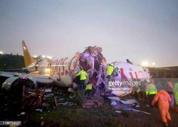 Officials work around the site after a passenger plane skidded off the runway in Istanbul Sabiha Gokcen International Airport, breaking into two, on...