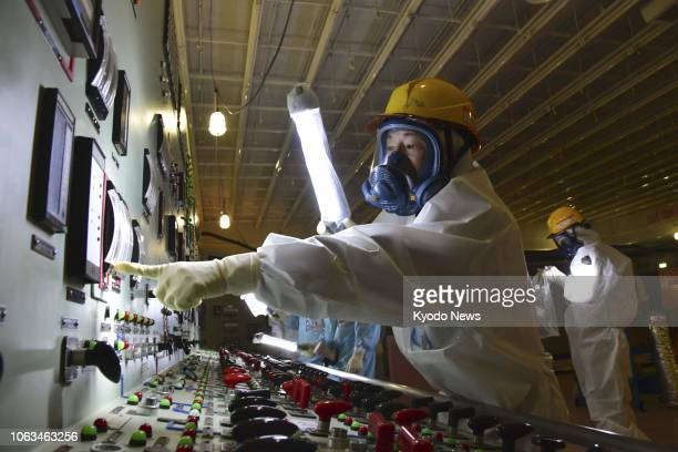 Officials work on Nov 15 in the main control room of the crippled Nos 3 and 4 reactors at the Fukushima Daiichi nuclear power plant in northeastern...