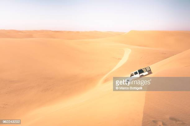 off-road vehicle driving on sand dunes - namib naukluft national park stock pictures, royalty-free photos & images
