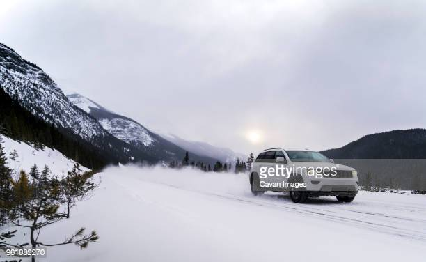 off-road vehicle moving on snowy field against cloudy sky - extreme weather stock photos and pictures