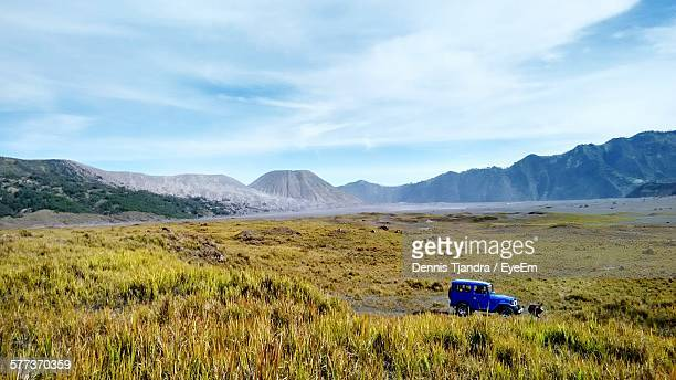 Off-Road Vehicle On Grassy Field Against Mountains And Cloudy Sky