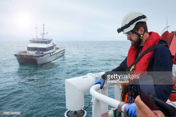 offshore manual high worker waiting for transfer vessel with wind-turbines behind him. - life jacket stock pictures, royalty-free photos & images