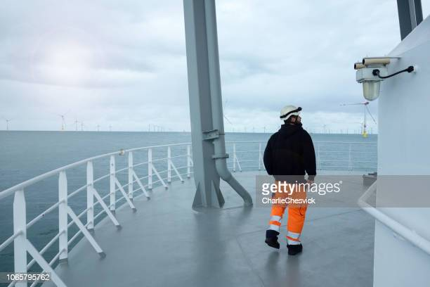 offshore manual worker walking on boat deck with wind-farm front of vessel. - industrial ship stock pictures, royalty-free photos & images