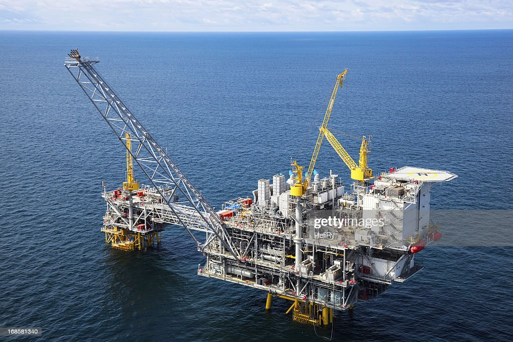 Offshore oil rig in a large body of water : Stock Photo