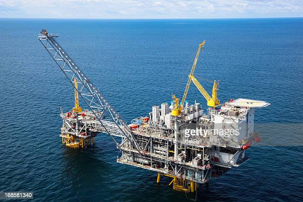 offshore oil rig in a large body of water - oil rig stock pictures, royalty-free photos & images