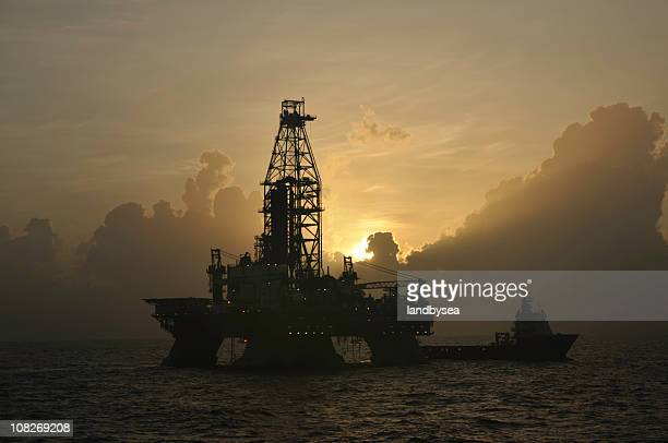 Offshore oil rig with vessel at sunrise
