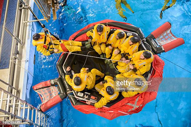 Offshore oil workers hoisted from raft in sea ditching survival training in pool facility, overhead view