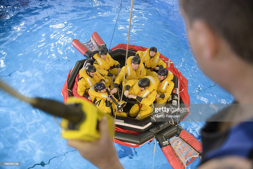 Offshore oil workers hoisted from raft in sea ditching survival training in pool facility : Stock Photo