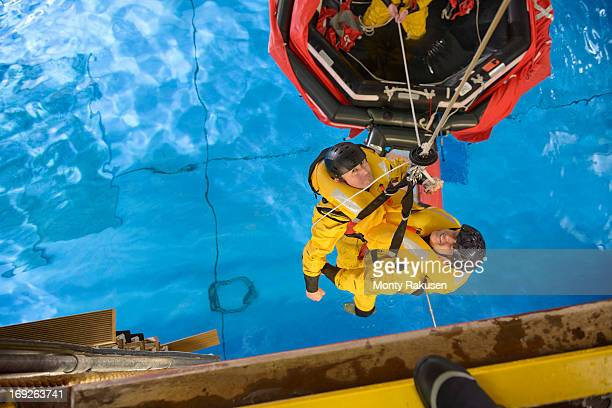 offshore oil workers hoisted from raft in sea ditching survival training in pool facility - redding sporten stockfoto's en -beelden