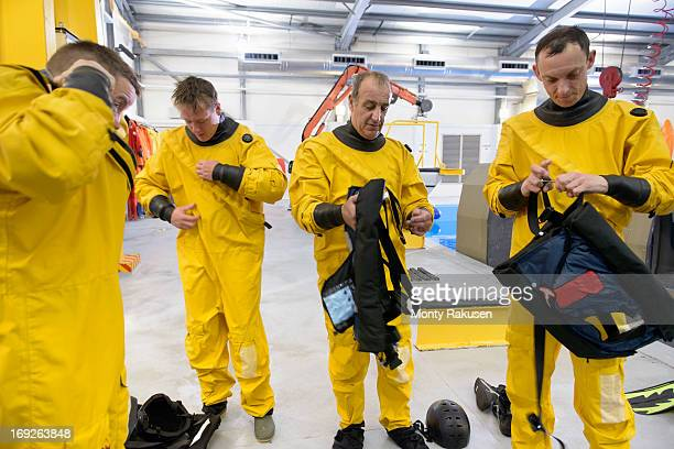 Offshore oil workers putting on diving equipment in training pool facility