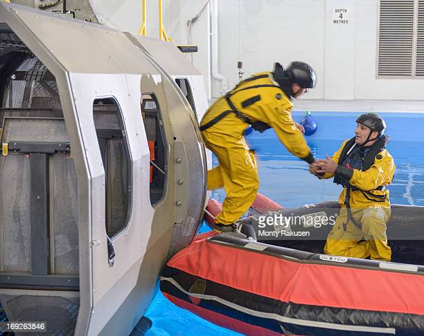 Offshore oil workers training in escape from helicopter simulator at training pool facility