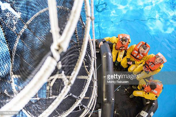 Offshore oil workers training in net escape simulation at training pool facility