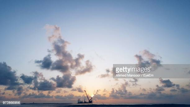 Offshore Platform In Sea Against Cloudy Sky At Sunset