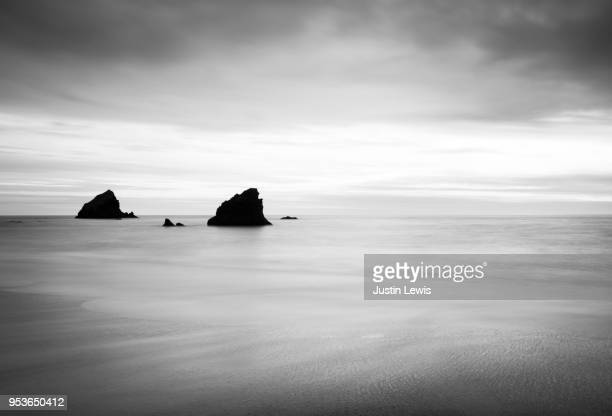 Offshore Rocks Surrounded by Calm, Soft-Focus Sea and Dramatic Storm Clouds