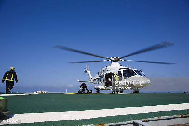 Offshore workers arrive by Sikorsky S76C helicopter aboard the Casablanca oil platform operated by Repsol SA in the Mediterranean Sea off the coast...