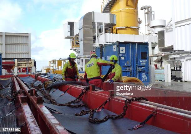 Offshore workers handle equipment aboard Songa Offshore's Songa Enabler rig operated by Statoil ASA in the Snohvit gas field in the Barents Sea off...