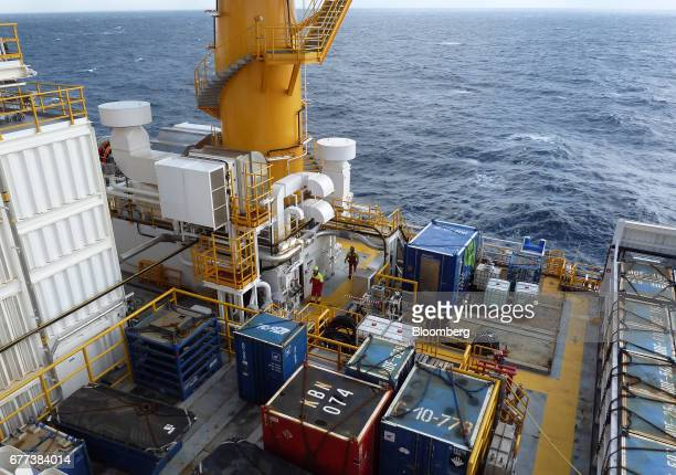 Offshore workers move aboard Songa Offshore's Songa Enabler rig operated by Statoil ASA in the Snohvit gas field in the Barents Sea off the coast of...