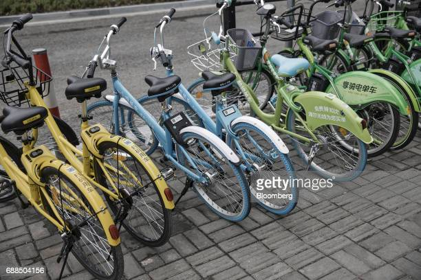 Ofo Inc left and second left Xiaoming Danche third and fourth left and other bicycles stand parked on a sidewalk in Shanghai China on Thursday May 25...