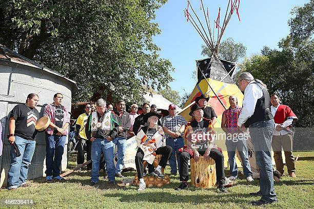 Ogalala Sioux Tribal President Bryan Brewer speaks to Willie Nelson and Neil Young during a ceremony where they were presented with decorated buffalo...