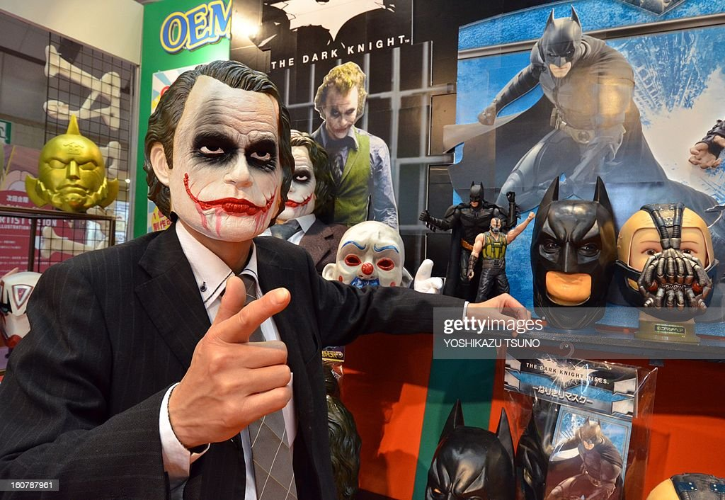 Ogawa Rubber, Japan's top rubber mask maker employee, wearing a rubber mask of Joker shows masks of Batman movie characters at the Tokyo International Gift Show in Tokyo on February 6, 2013. The masks will go on sale here soon. AFP PHOTO / Yoshikazu TSUNO