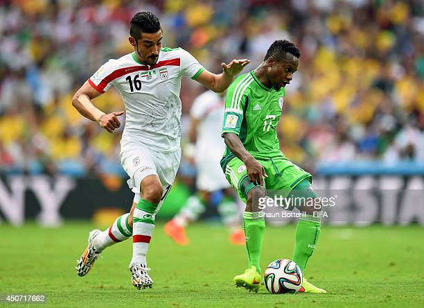 Ogenyi Onazi of Nigeria is chased by Reza Ghoochannejhad of Iran during the 2014 FIFA World Cup Brazil Group F match between Iran and Nigeria at...