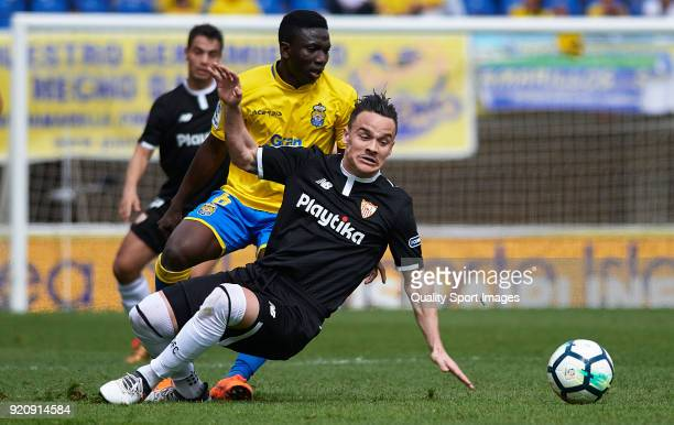 Oghenekaro Etebo of Las Palmas competes for the ball with Roque Mesa of Sevilla during the La Liga match between Las Palmas and Sevilla at Estadio...