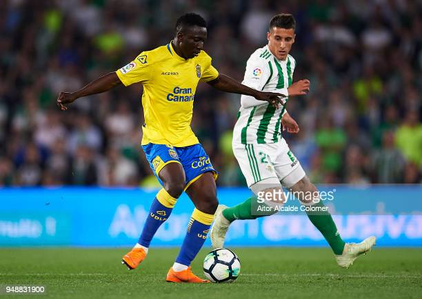 Oghenekaro Peter Etebo of Union Deportiva Las Palmas being followed by Cristian Tello of Real Betis Balompie during the La Liga match between Real...