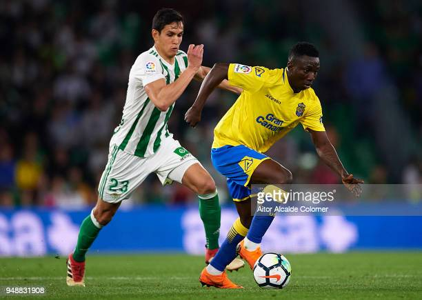 Oghenekaro Peter Etebo of Union Deportiva Las Palmas being followed by Aissa Mandi of Real Betis Balompie during the La Liga match between Real Betis...