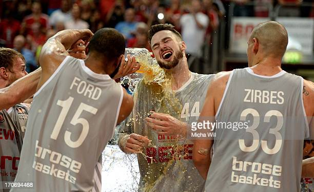 Ogilvy of Bamberg receives a beer shower from his teammates Sharrod Ford and Maik Zirbes after winning the finals of the Beko BBL playoffs against...