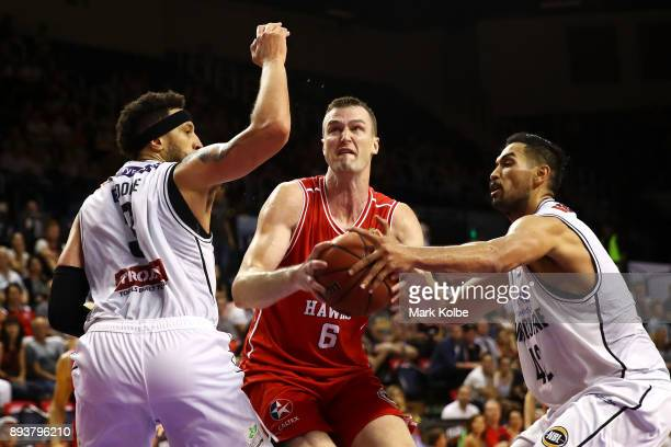 J Ogilvy of the Hawks drives to the basket under pressure from Josh Boone and Tai Wesley of Melbourne United during the round 10 NBL match between...