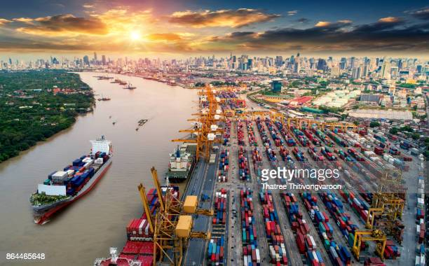 ogistics and transportation of Container Cargo ship and Cargo plane with working crane bridge in shipyard at sunrise