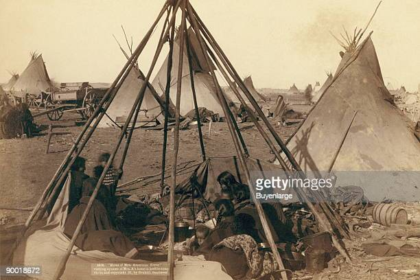 Oglala women and children seated inside an uncovered tipi frame in an encampment--most are looking away from the camera--probably on or near Pine...