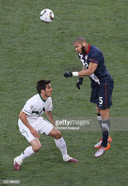 Oguchi Onyewu of the United States wins the header under pressure from Zlatan Ljubijankic of Slovenia during the 2010 FIFA World Cup South Africa...