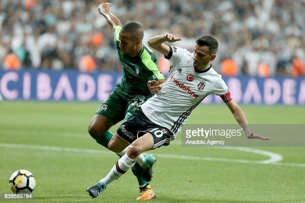 Oguzhan Ozyakup of Besiktas vies for the ball against Paul Ekong of Bursaspor during a Turkish Super Lig soccer match between Besiktas JK and...