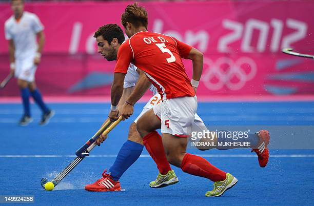 Oh Dae Kyun of South Korea fights for the puck with Valentin Verga of the Netherlands during the men's field hockey preliminary round match between...